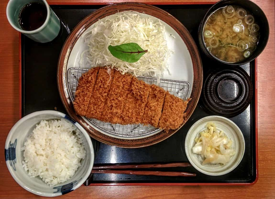 katsu dish served with rice, shredded cabbage with dressing, pickles and miso soup